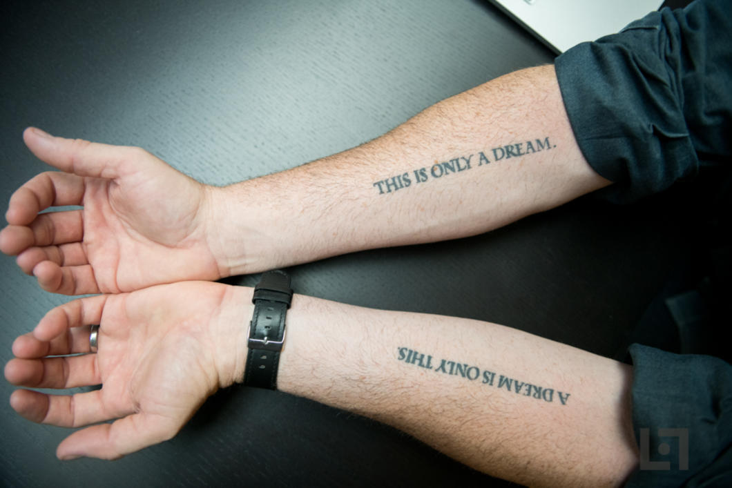 photo of mans arms with tattoos saying this is only a dream