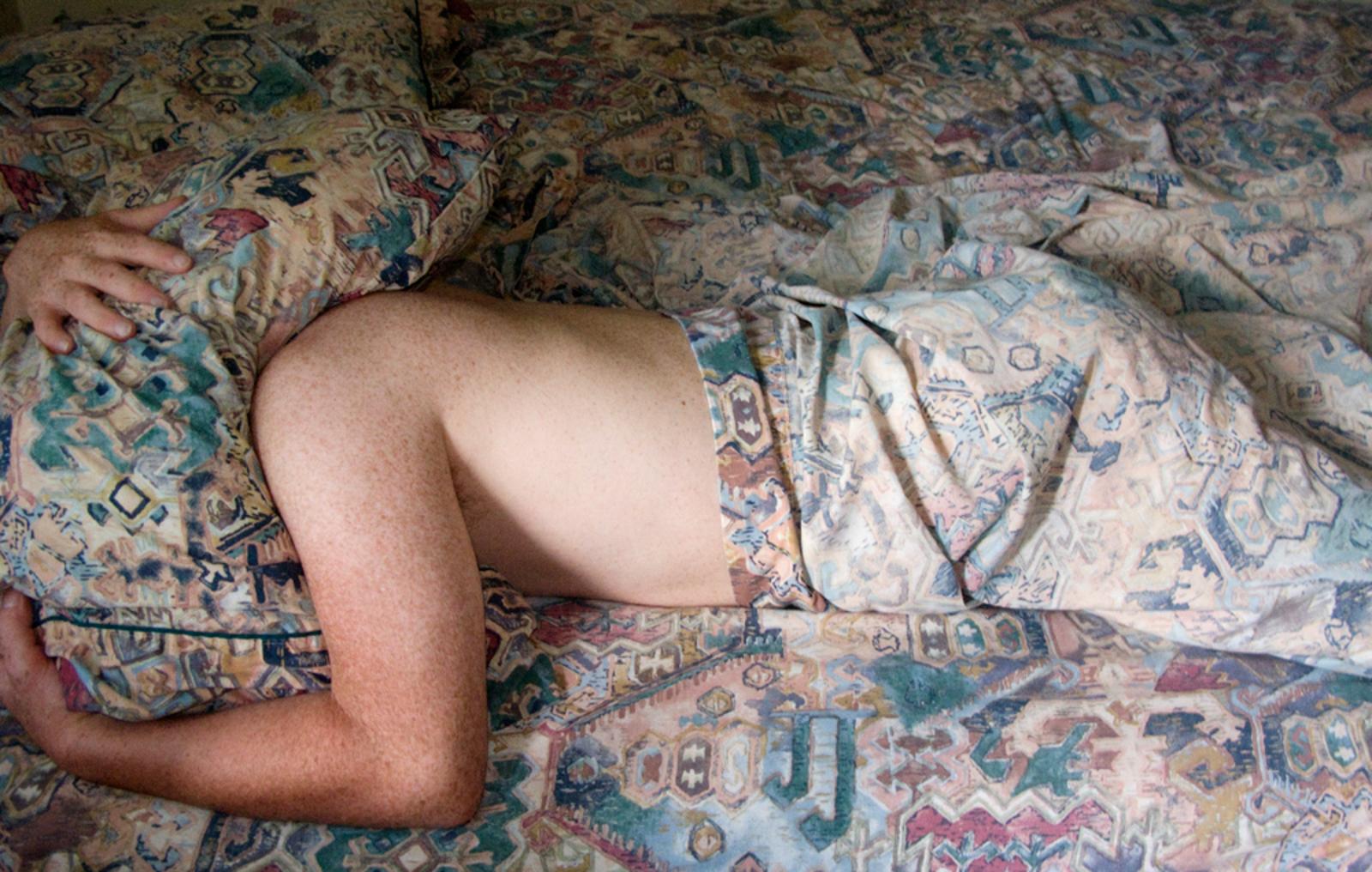 man hiding under sheets