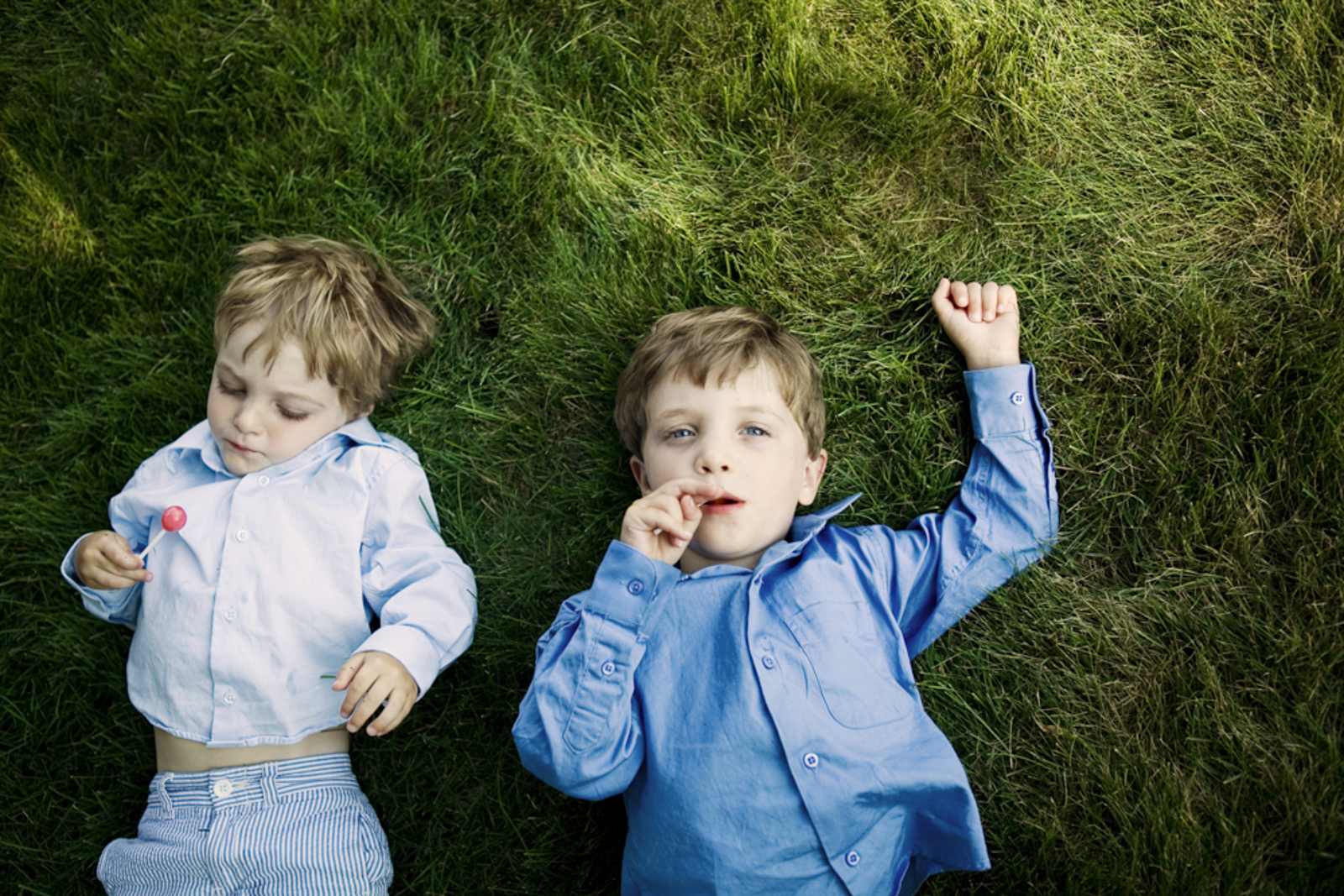 two young boys with lollipops on grass