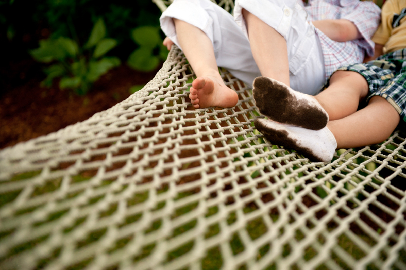 two people on rope hammock one with dirty socks
