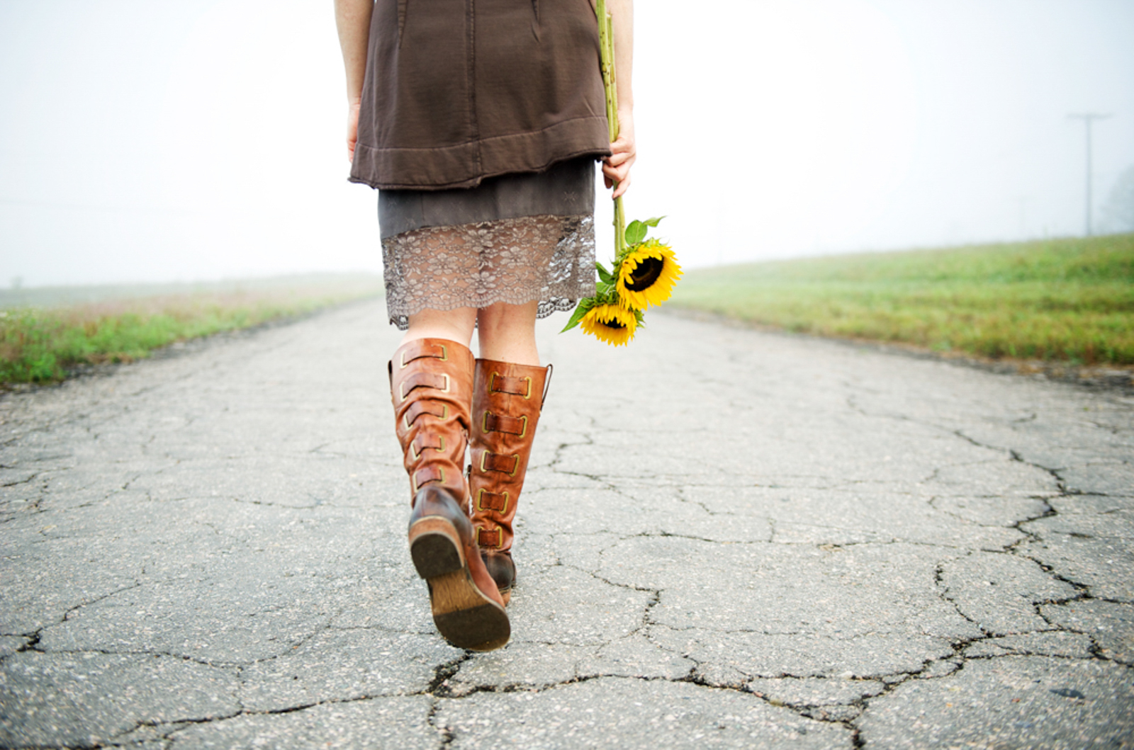 woman walking along road with sunflowers